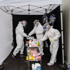 Tre personer i vita skyddskläder och ansiktsskydd tar emot coronaprov vid en container, som fungerar som en drive-in-testning.