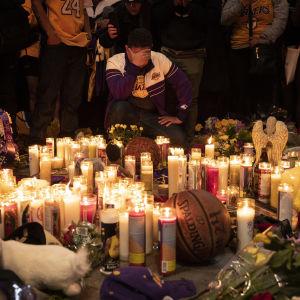 Person håller sig för ansiktet framför tända ljus för att hedra Kobe Bryant.