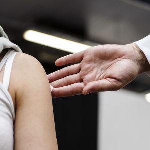 En ung kvinna får plåster på armen efter vaccination