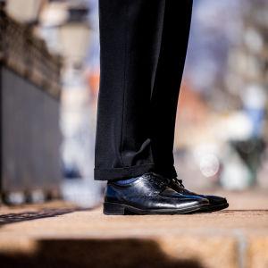Anonyymin pukuun pukeutuneen henkilön jalat.