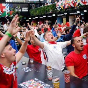 Fotbollssupportrar sitter på en uteservering med händerna i vädret.