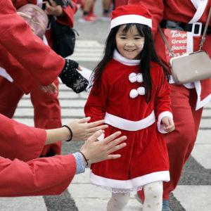 En japansk flicka klädd i tomtedräkt deltog i ett välgörenhetslopp i Tokyo den 22 december.