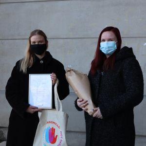 En ljushårig kvinna och en mörkhårig kvinna, som båda har munskydd på sig, håller upp ett diplom och en blombukett som de fått av Röda Korset.