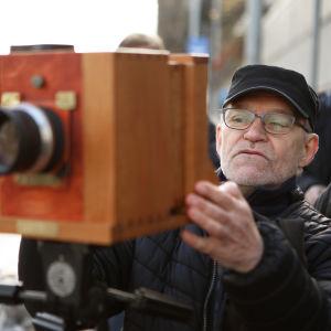 Mies kuvaa vanhalla kameralla toisintoa Suomen ensimmäisestä valokuvasta Turun Humalistonkadulla.