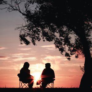 två personer sitter bredvid varann vid solnedgången
