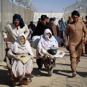 Afghanska män skuffar två afghanska kvinnor i rullstol över gränsen från Pakistan till Afghanistan.