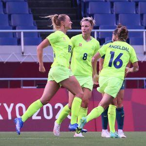 Fridolina Rolfö jublar efter att ha gjort mål, omgiven av två andra svenska spelare.