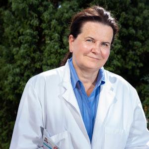 Nainen katsoo kameraan lääkärintakki yllään. Taustalla vihreä puska.