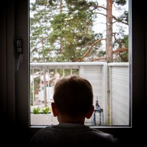 Ett barn sitter och tittar ut genom ett fönster.