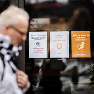 Två personer går förbi en restaurang. På dörren finns skyltar som meddelar att restaurangen är stängd på grund av coronarestriktioner.