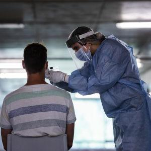 En skötare tar coronatest av en person.