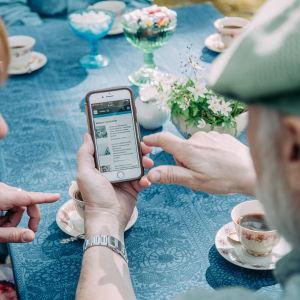 Nainen ja mies katselevat älypuhelimen näytöltä Ylen verkkosivuja.