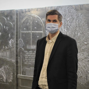 Man med munskydd står framför en tavla.