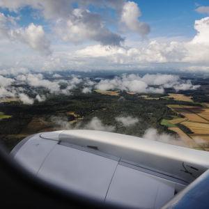En bild tagen genom ett flygplansfönster. Utanför fönstret syns en vy över åkrar i Finland. Bilden är tagen i september 2020.