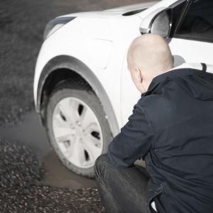 En man står vid en vit bil på en parkeringsplats. Bilens däck är i en vattenfylld grop. Mannen ser oroligt på däcket.