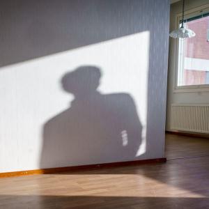 Tyhjä myytävänä oleva asunto, seinällä ihmisen varjo.