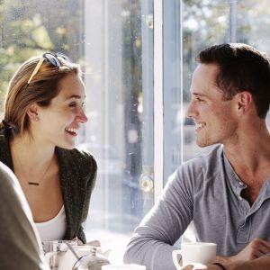 Tre personer sitter vid ett kaffebord.