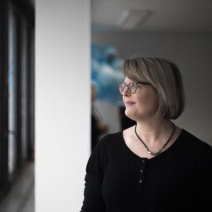 En kvinna ser ut genom ett fönster. Bakgrunden är relativt mörk.