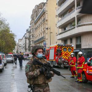 Tungt beväpnad soldat patrullerar bland utryckningsfordon på en gata i Paris.