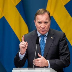 Stefan Löfven på pressträff framför svenska flaggor, med pekfingret höjt i förmaning.