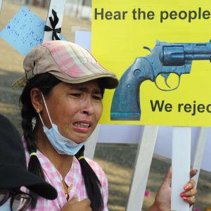 """En ung kvinna med skärmmössa står framför ett gult plakat med en revolver som fått knut på pipan. Plakatet har texten """"Hear the people's voice. We reject coup""""."""