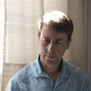 En man sitter framför ett fönster. Bilden är på hans ansikte. Hans ögon är stängda.