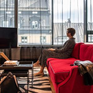 Nainen istuu hotellihuoneen sohvalla ja katselee maisemaa.