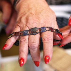 En hand med röda naglar provar ett armband gjort av landskapsvapen hopsatta med små kedjor mellan dem.
