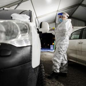 En drive-inteststation, med en vit bil och en sjukskötare i skyddsutrustning.