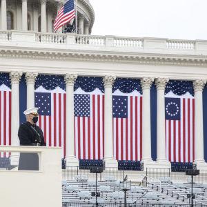 En soldat i paraduniform framför Capitolium. Bakom honom syns flera olika versioner av USAs flaggor som hängts upp på capitoliumbyggnaden i en prydlig rad.
