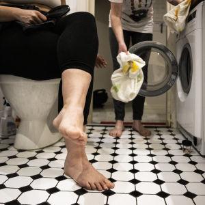 Henkilö täyttää pesukonetta ja toinen henkilö istuu vessanpytyn anten päällä hiusharja kädessään.