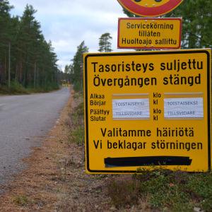 Några gula skyltar vid en väg som upplyser allmänheten om att en plankorsning är stängd tillsvidare.
