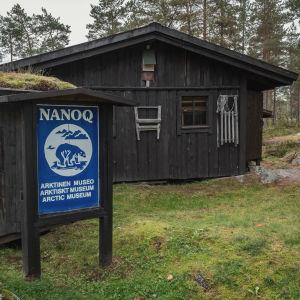 Sinivalkoinen kyltti jossa teksti Nanoq ja jääkarhun kuva, tummia mökkejä taustalla
