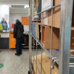 I förgrunden postpaket som står på en hylla. I bakgrunden personer som hämtar ut paket från en postkassa.