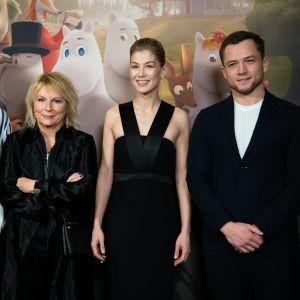 Edvin Endre, Jennifer Saunders, Rosamund Pike ja Taron Egerton seisovat muumien kuvausseinän edessä vierekkäin hymyillen.