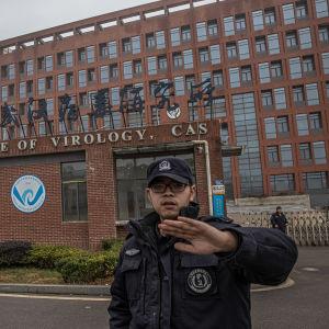 Suuri tiiliseinäinen rakennus, jossa lukee Wuhan Institute Of Virology. Vartija koittaa kedällään estää kuvaajaa ottamasta kuvaa rakennuksesta.
