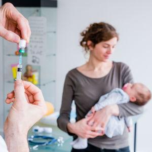 En läkare förbereder vaccinationsspruta för en baby.