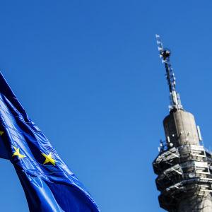 Kuvassa liehuu Euroopan unionin lippu, taustalla näkyy Pasilan linkkitorni.