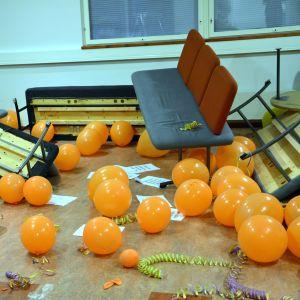 Rum fullt av ballonger, serpentiner och felsvängda soffor.