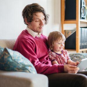 Mies ja lapsi katsovat yhdessä ohjelmaa tabletilla.