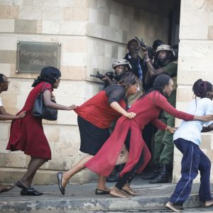 Evakuerade anställda och civila flyr från hotellet under polisens skydd