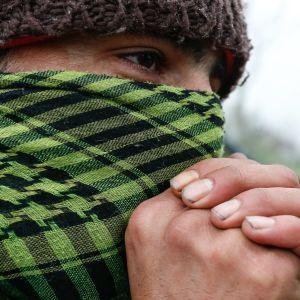 Arkivbild på en migrant i belgiska Zeerugge som fryser om händerna.