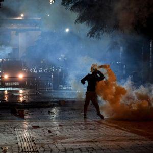 En demonstrant kastar tillbaka polisens tårgasgranater under lördagskvällens sammandrabbningar i Tirana.