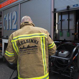 palomies huoltaa paloautoa Helsingin keskuspelastusaseman pihalla
