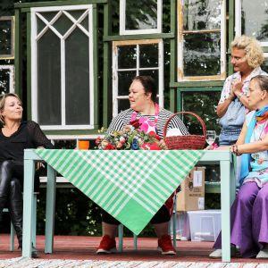 Grupp kvinnor sitter runt ett bord.