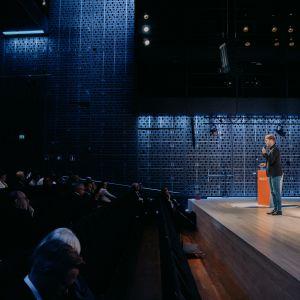 Man speaking on the stage of Musiikkitalo talking to the audience.