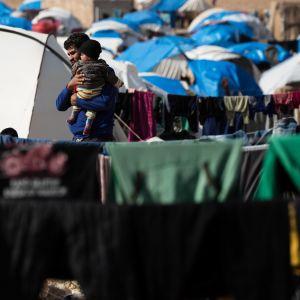 Mies kantaa lastaan telttarivistön keskellä Ain Issan pakolaisleirillä Syyriassa.