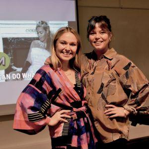 Två unga glada kvinnor framför Power Point-presentation.