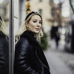 Alexandra står lutad mot en vägg. Hennes reflektion syns bakom henne och hon tittar rakt in i kameran med ett reserverat leende.
