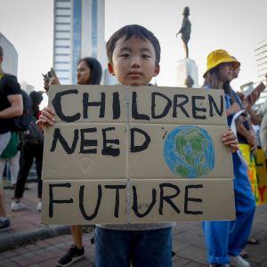 """En ung pojke håller i en skylt med texten """"Children need future"""" (barn behöver en framtid) under en klimatstrejk i Bangkok, Thailand i november 2019."""